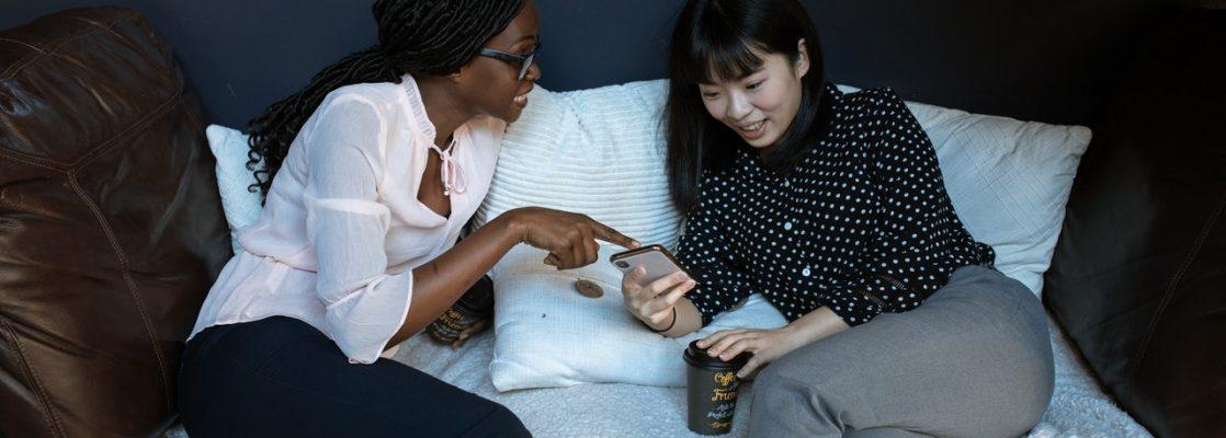 Deux femme assises sur canapé discutant heureuse