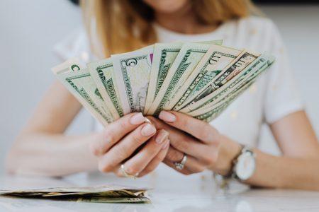 Femme tenant une liasse de billets entre ses mains