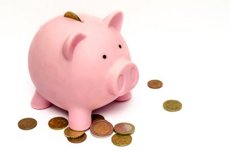 Tirelire cochon rose avec monnaie ressortant
