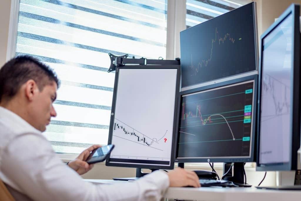 Homme travaillant sur une station trading pour observer les bourses