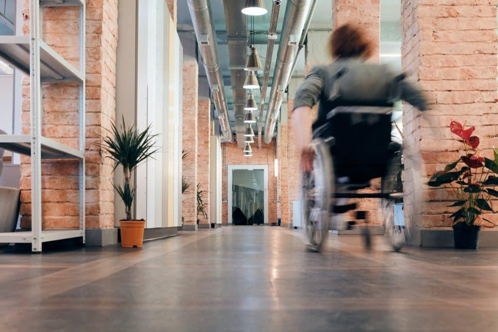 Femme en fauteuil roulant dans un couloir