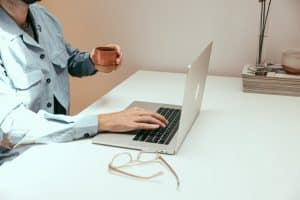 Homme en télétravail, travaillant sur son ordinateur et buvant un café