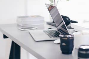 Bureau avec un ordinateur portable type Macbook de Apple, un mug, des zoom